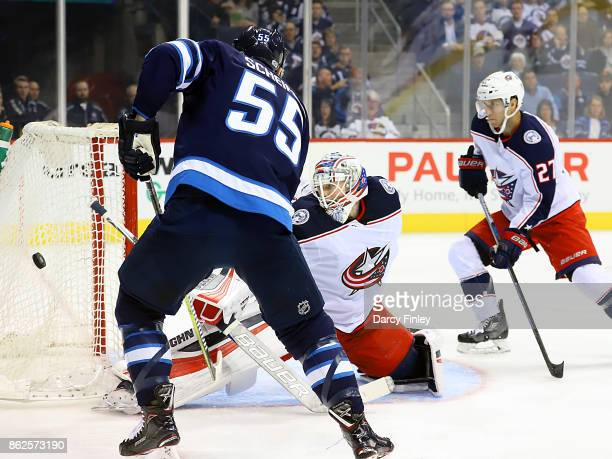 Mark Scheifele of the Winnipeg Jets chips the puck wide of the goal as goaltender Joonas Korpisalo of the Columbus Blue Jackets guards the net during...