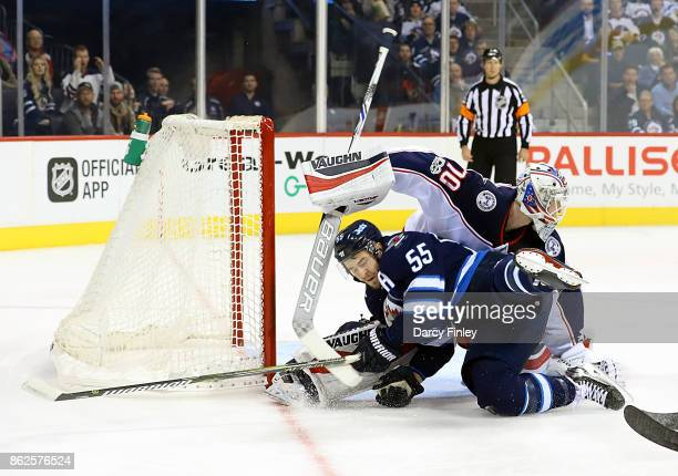Mark Scheifele of the Winnipeg Jets crashes into goaltender Joonas Korpisalo of the Columbus Blue Jackets during first period action at the Bell MTS...