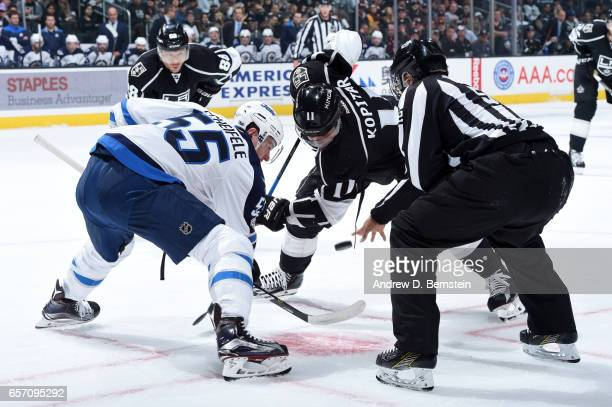 Mark Scheifele of the Winnipeg Jets faces off against Anze Kopitar of the Los Angeles Kings at STAPLES Center on March 23 2017 in Los Angeles...