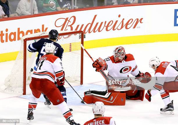 Mark Scheifele of the Winnipeg Jets Jordan Staal and goaltender Scott Darling of the Carolina Hurricanes watch as a shot by Nikolaj Ehlers hits the...