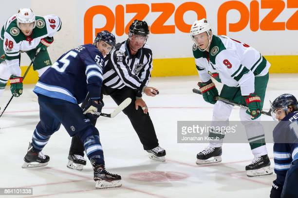 Mark Scheifele of the Winnipeg Jets linesman Derek Nansen and Mikko Koivu of the Minnesota Wild look on as they await a second period faceoff at the...