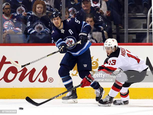 Mark Scheifele of the Winnipeg Jets makes a pass up the ice past a defending Nico Hischier of the New Jersey Devils during first period action at the...
