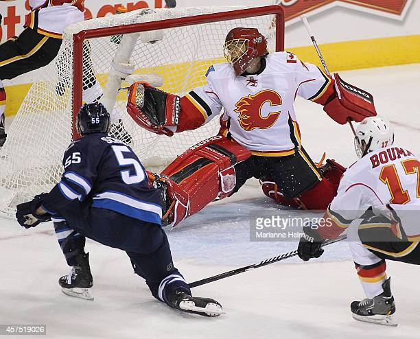 Mark Scheifele of the Winnipeg Jets scores against Jonas Hiller of the Calgary Flames in first period action in an NHL game at the MTS Centre on...