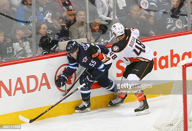 Mark Scheifele of the Winnipeg Jets slips past the check of Colby Robak of the Anaheim Ducks during third period action on December 7 2014 at the MTS...