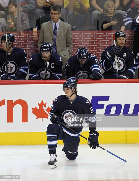 Mark Scheifele of the Winnipeg Jets stretches on the ice before the start of the third period while teammates James Wright Andrew Ladd Matt Halischuk...