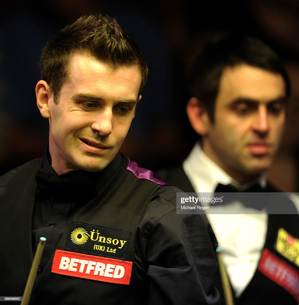 Mark Selby of England eyes a shot as Ronnie O'Sullivan of England looks on during the quarter finals of the Betfredcom World Snooker Championships at...