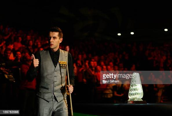 Mark Selby of England gives the thumbs up to the camera as he walks past The Masters Trophy during The Masters Final between Mark Selby of England...