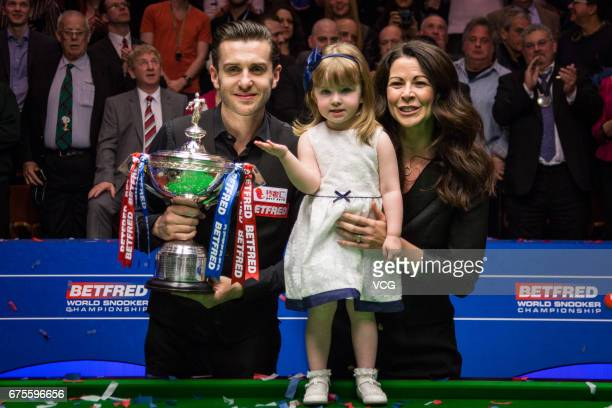 Mark Selby of England holding his trophy poses with his daughter and wife after winning the final match against John Higgins of Scotland on day...