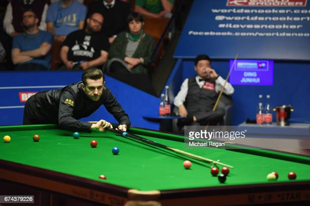 Mark Selby of England plays a shot as Ding Junhui of China looks on during their semifinal match on day 14 of the World Snooker Championship at the...