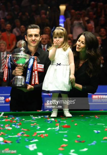 Mark Selby of England poses with the trophy with his duaghter Sofia and wife Vikki after beating John Higgins of Scotland in the final of the World...