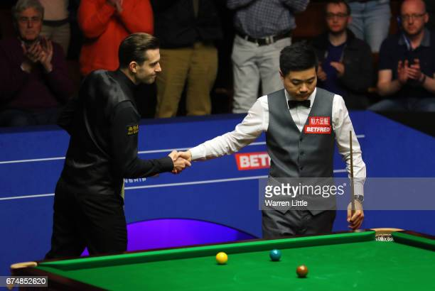 Mark Selby of England shakes hands with Ding Junhui of China after winning the semi final match on day fifteen of Betfred World Championship 2017 at...
