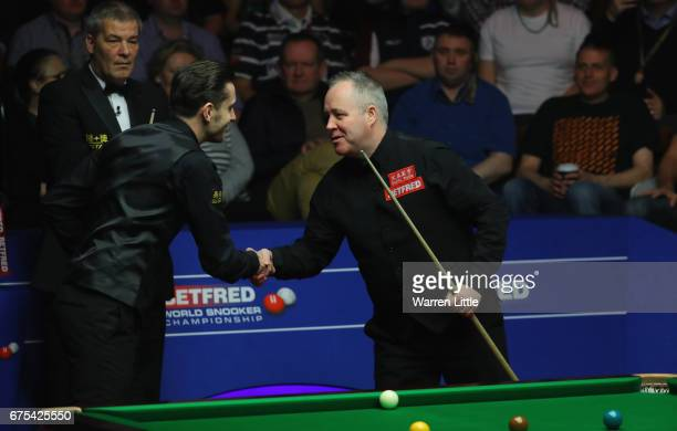 Mark Selby of England shankes hands with John Higgins of Scotland ahead of the final of the World Snooker Championship on day seventeen at Crucible...