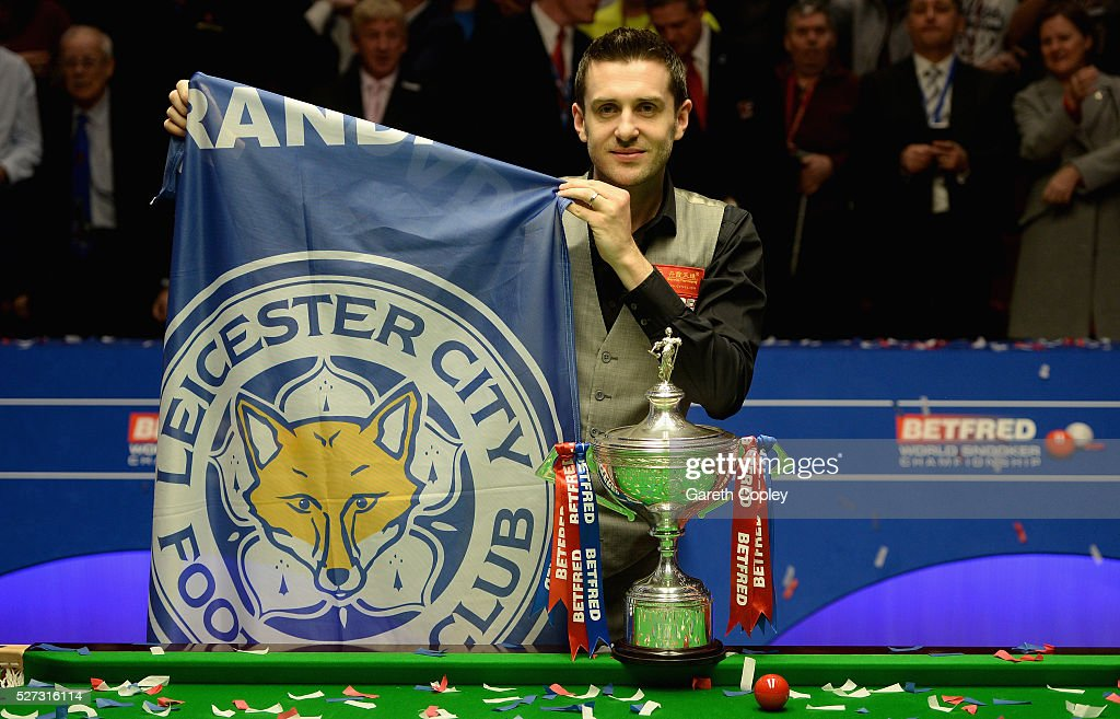 Mark Selby with a Leicester City football club flag after lifting the trophy after beating Ding Junhui to win the World Snooker Championship final at...