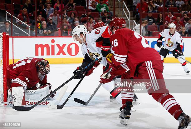 Mark Stone of the Ottawa Senators attempts to push the puck past goaltender Mike Smith of the Arizona Coyotes as he is defended by Michael Stone...