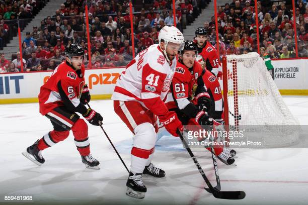 Mark Stone of the Ottawa Senators battles for the loose puck against Luke Glendening of the Detroit Red Wings as Chris Wideman of the Ottawa Senators...