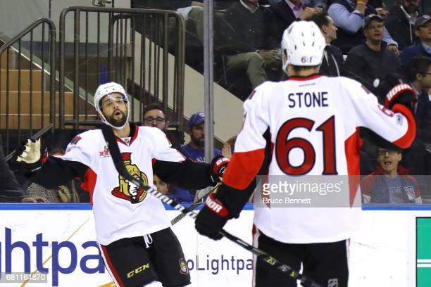 Mark Stone of the Ottawa Senators celebrates with teammate Clarke MacArthur after scoring a goal against Henrik Lundqvist of the New York Rangers...
