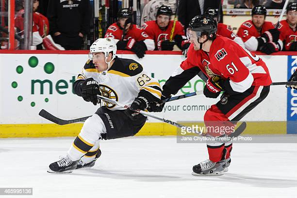 Mark Stone of the Ottawa Senators defends against Brad Marchand of the Boston Bruins at Canadian Tire Centre on March 10 2015 in Ottawa Ontario Canada