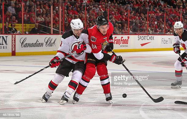 Mark Stone of the Ottawa Senators is checked off the puck by Stephen Gionta of the New Jersey Devils at Canadian Tire Centre on October 25 2014 in...