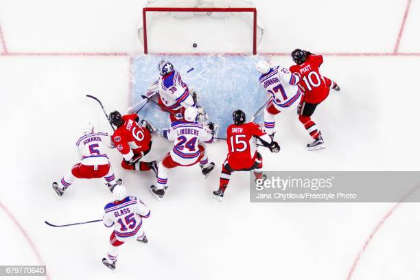 Mark Stone of the Ottawa Senators scores a first period goal against Henrik Lundqvist of the New York Rangers as Zack Smith and Tom Pyatt of the...