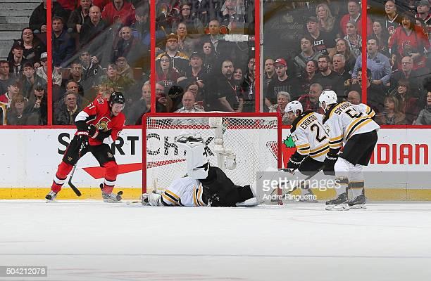 Mark Stone of the Ottawa Senators scores the overtime winning goal against Tuukka Rask of the Boston Bruins as Loui Eriksson and Ryan Spooner look on...