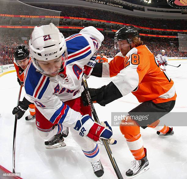 Mark Streit and Claude Giroux of the Philadelphia Flyers battle in the corner with Derek Stepan of the New York Rangers on February 28 2015 at the...