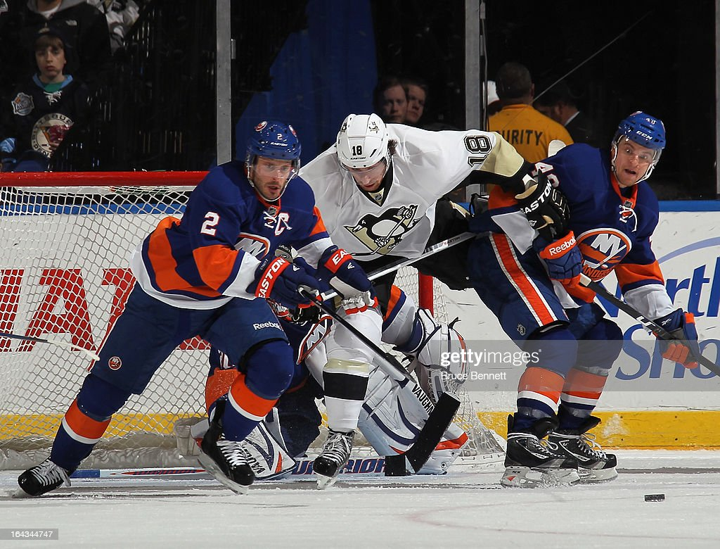 Mark Streit #2 and Michael Grabner #40 of the New York Islanders defend against James Neal #18 of the Pittsburgh Penguins at Nassau Veterans Memorial Coliseum on March 22, 2013 in Uniondale, New York.