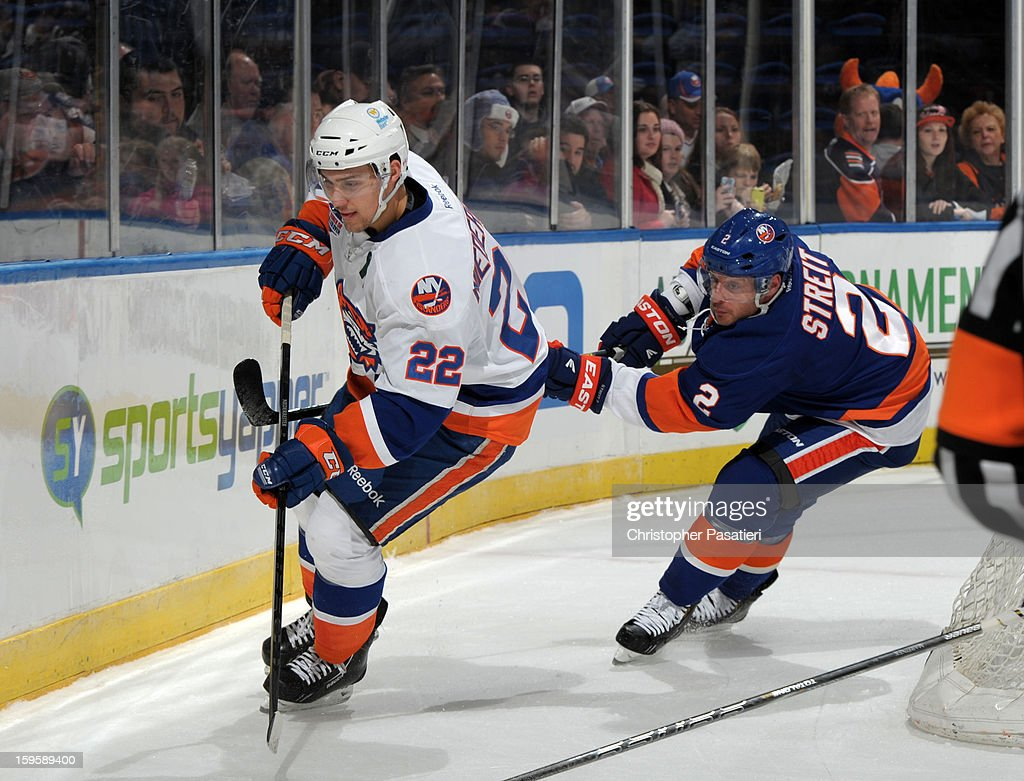 Mark Streit #2 of Team Blue reaches for Nino Niederreiter #22 of Team White during a scrimmage match between players of the New York Islanders and Bridgeport Sound Tigers on January 16, 2013 at Nassau Veterans Memorial Coliseum in Uniondale, New York.