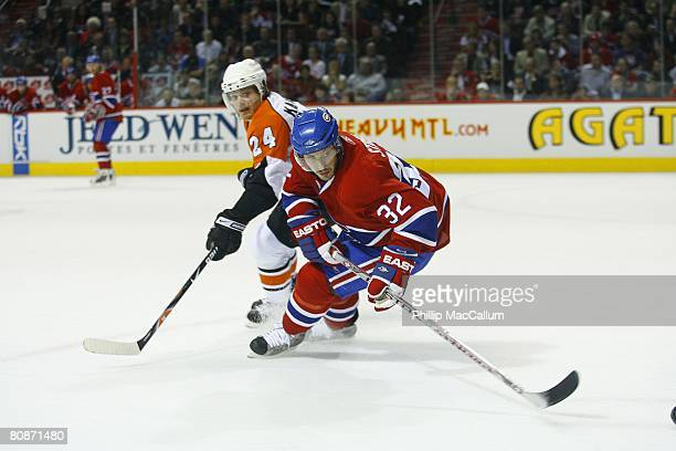 Mark Streit of the Montreal Canadiens passes the puck against Sami Kapanen of the Philadelphia Flyers during Game One of the Eastern Conference...
