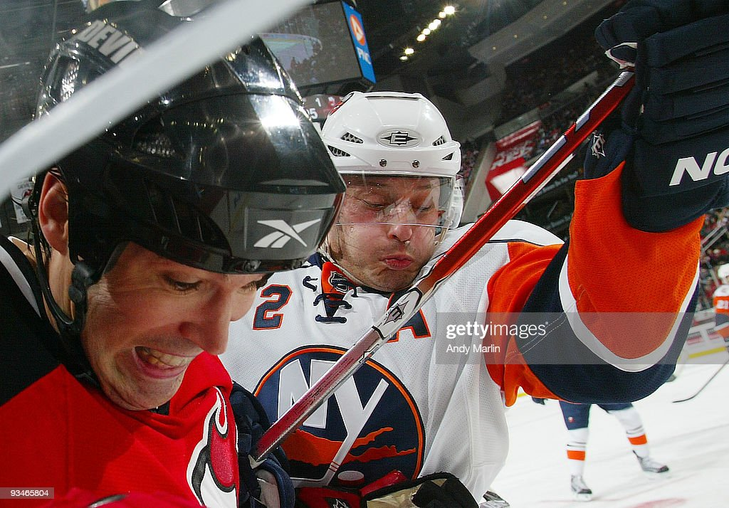 Mark Streit of the New York Islanders and Brian Rolston of the New Jersey Devils battle hard during their game at the Prudential Center on November...