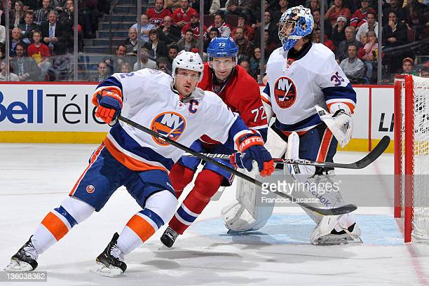 Mark Streit of the New York Islanders and Erik Cole of the Montreal Canadiens follow the play in front of goalie Al Montoya during the NHL game on...