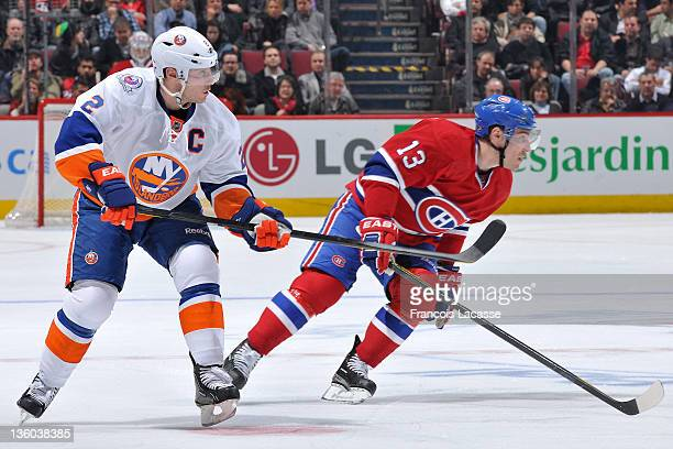 Mark Streit of the New York Islanders and Mike Cammalleri of the Montreal Canadiens follow the play during the NHL game on December 13 2011 at the...