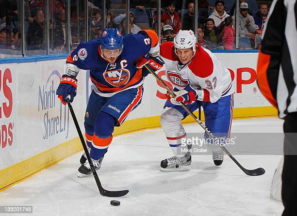 Mark Streit of the New York Islanders controls the puck in front of Travis Moen of the Montreal Canadiens at Nassau Veterans Memorial Coliseum on...