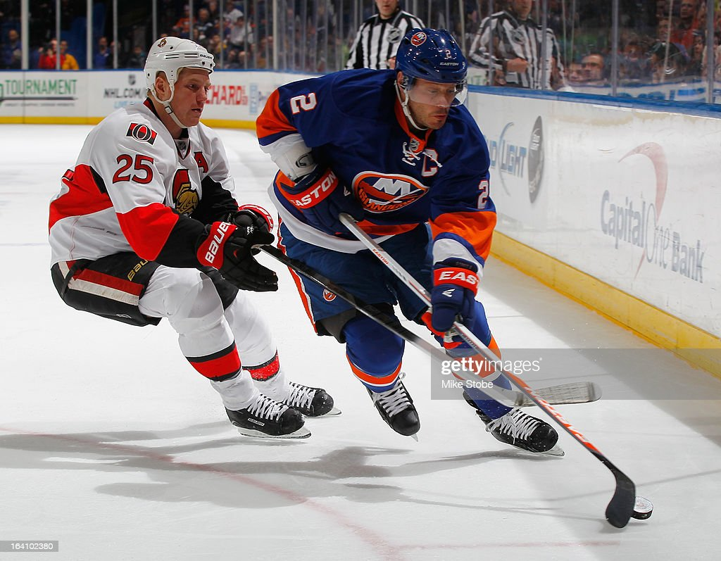 <a gi-track='captionPersonalityLinkClicked' href=/galleries/search?phrase=Mark+Streit&family=editorial&specificpeople=636976 ng-click='$event.stopPropagation()'>Mark Streit</a> #2 of the New York Islanders controls the puck in front of Chris Neil #25 of the Ottawa Senators at Nassau Veterans Memorial Coliseum on March 19, 2013 in Uniondale, New York. The Senators defeated the Islanders 5-3.