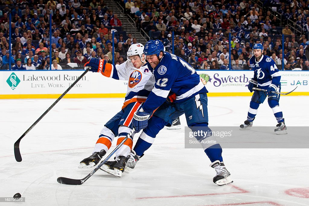 <a gi-track='captionPersonalityLinkClicked' href=/galleries/search?phrase=Mark+Streit&family=editorial&specificpeople=636976 ng-click='$event.stopPropagation()'>Mark Streit</a> #2 of the New York Islanders fights for control of the puck with <a gi-track='captionPersonalityLinkClicked' href=/galleries/search?phrase=Ryan+Malone&family=editorial&specificpeople=206964 ng-click='$event.stopPropagation()'>Ryan Malone</a> #12 of the Tampa Bay Lightning during the third period of the game at the Tampa Bay Times Forum on March 14, 2013 in Tampa, Florida.