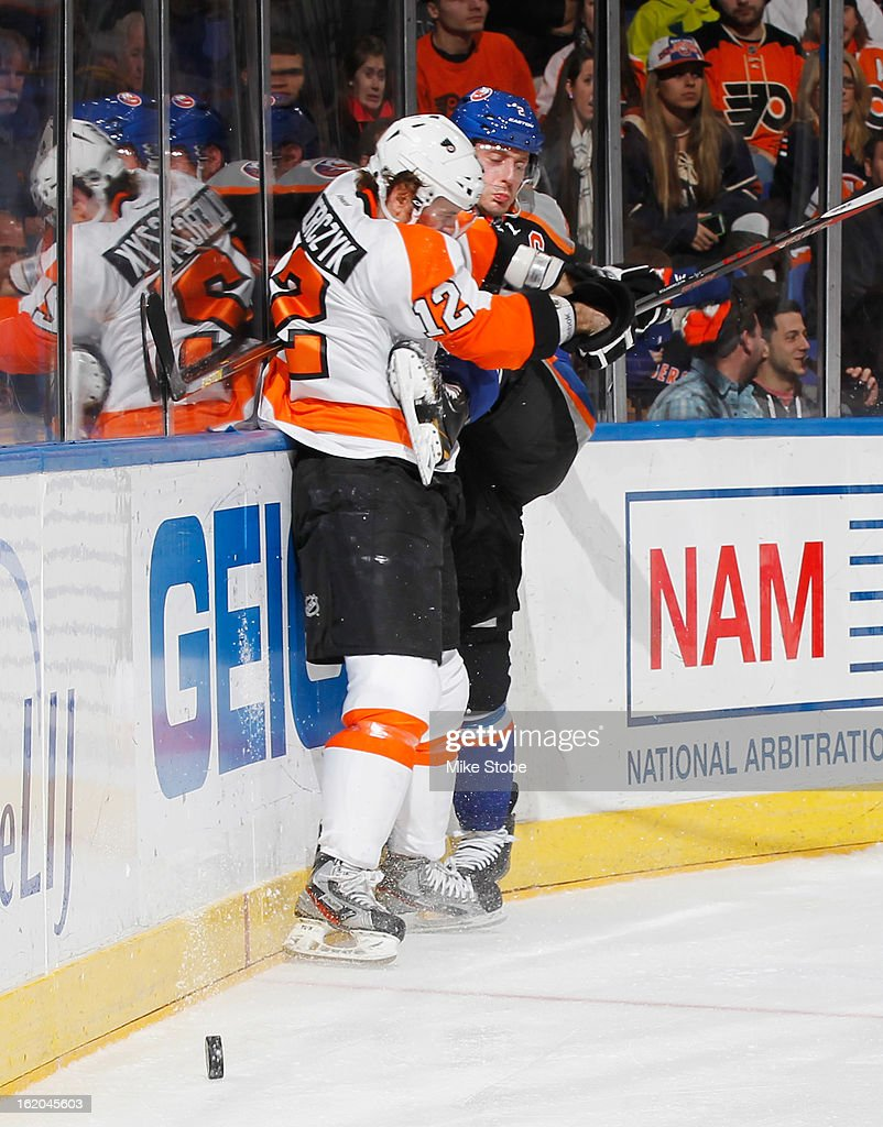 Mark Streit #2 of the New York Islanders is checked by Harry Zolnierczyk #12 of the Philadelphia Flyers at Nassau Veterans Memorial Coliseum on February 18, 2013 in Uniondale, New York. The Islanders were shut out by the Flyers 7-0.