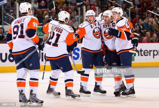 Mark Streit of the New York Islanders is congratulated by teammates John Tavares Kyle Okposo Doug Weight and Josh Bailey after Streit scored a second...