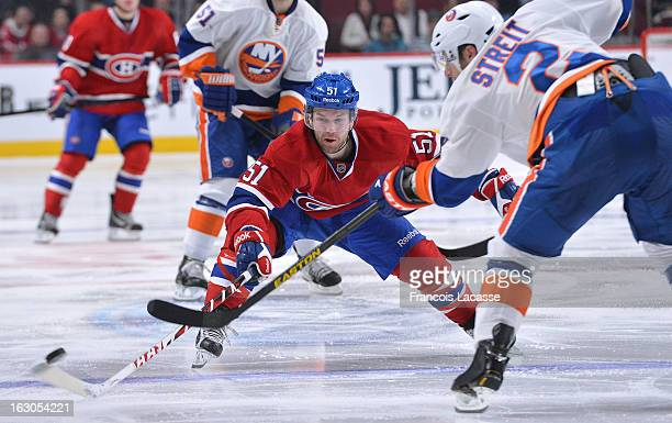 Mark Streit of the New York Islanders passes the puck against pressure from David Desharnais of the Montreal Canadiens during an NHL game on February...