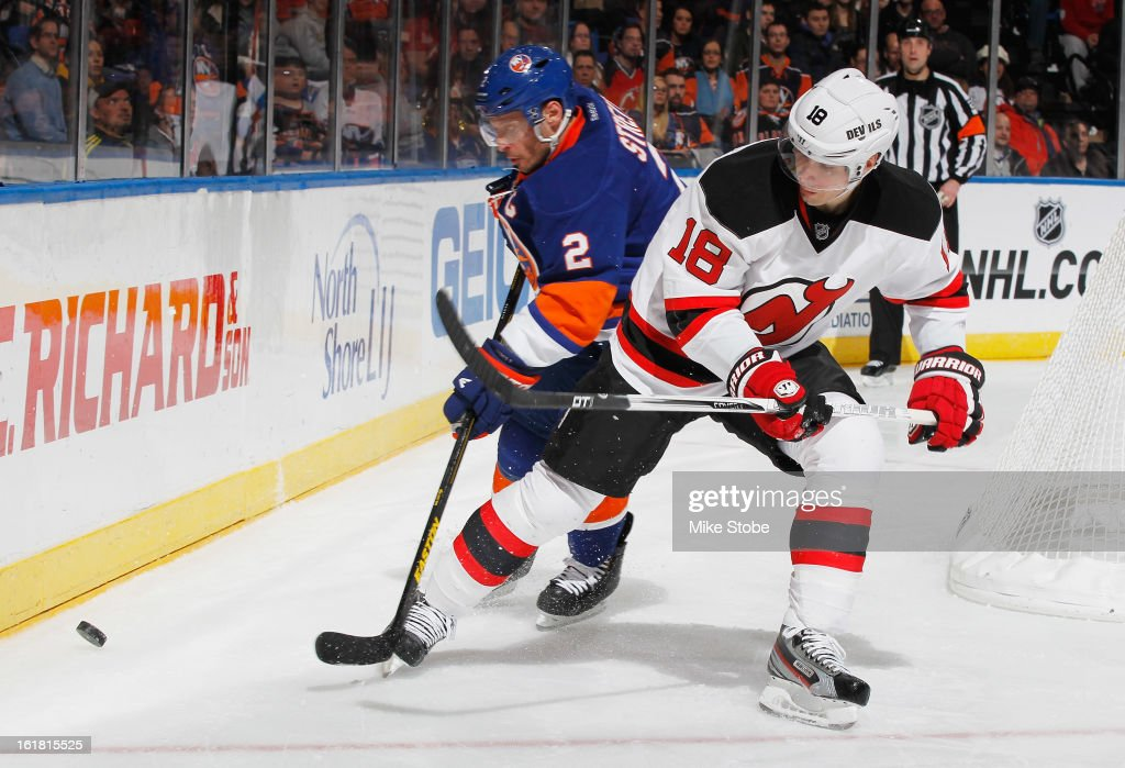 Mark Streit #2 of the New York Islanders pursues the puck against Steve Bernier #18 of the New Jersey Devils at Nassau Veterans Memorial Coliseum on February 16, 2013 in Uniondale, New York.