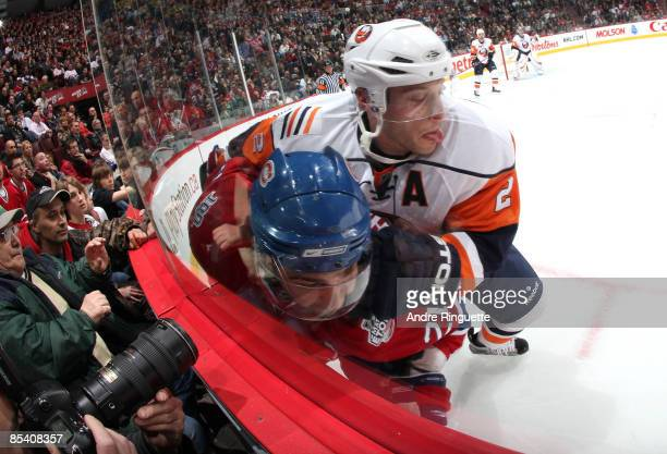 Mark Streit of the New York Islanders squeezes Christopher Higgins of the Montreal Canadiens into the boards at the Bell Centre on March 12 2009 in...