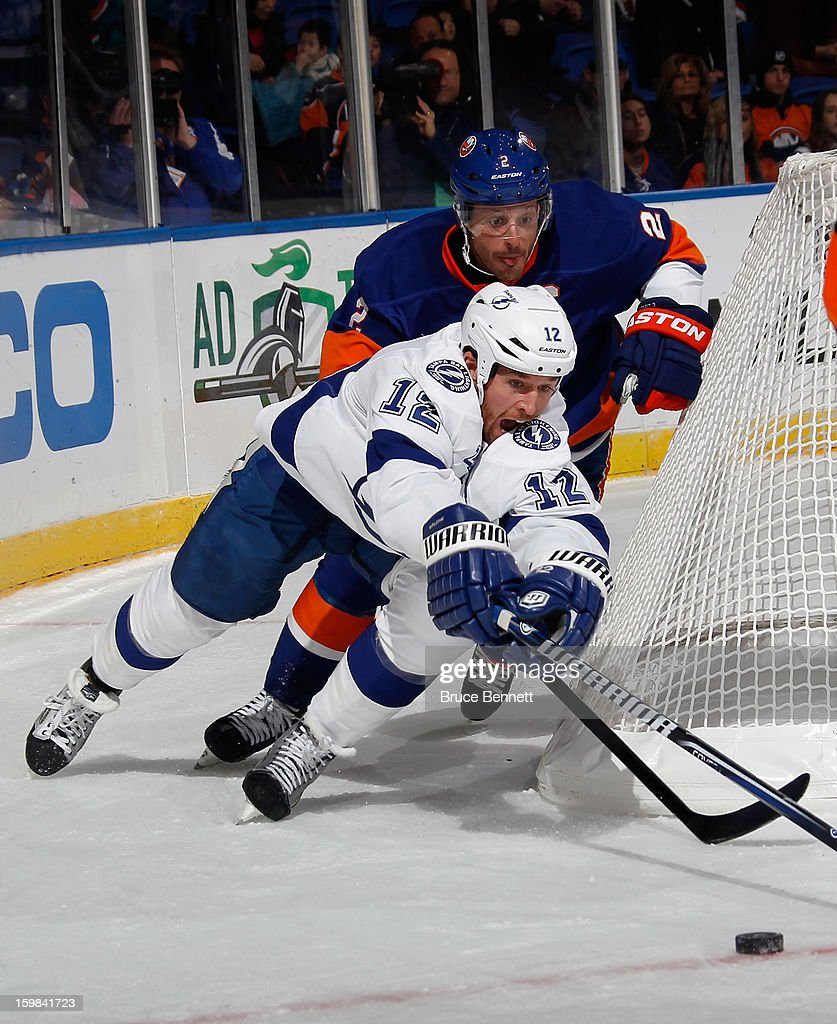 Mark Streit #2 of the New York Islanders trips up Ryan Malone #12 of the Tampa Bay Lightning in the third period at the Nassau Veterans Memorial Coliseum on January 21, 2013 in Uniondale, New York. The Islanders defeated the Lightning 4-3.