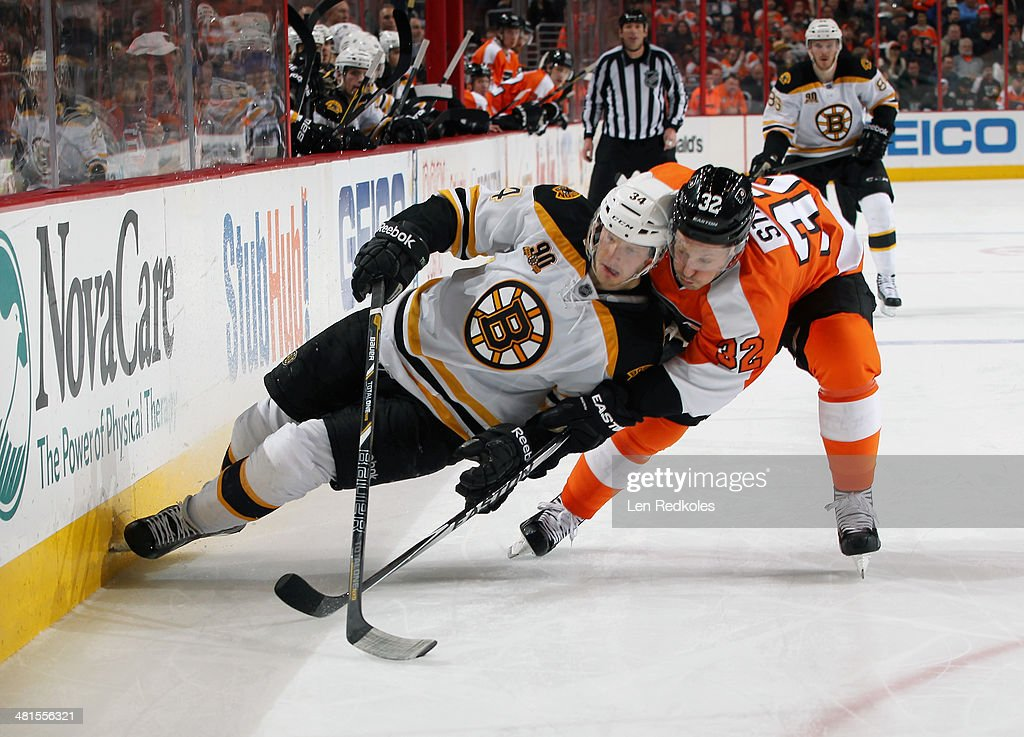 Mark Streit #32 of the Philadelphia Flyers checks Carl Soderberg #34 of the Boston Bruins into the boards on March 30, 2014 at the Wells Fargo Center in Philadelphia, Pennsylvania.