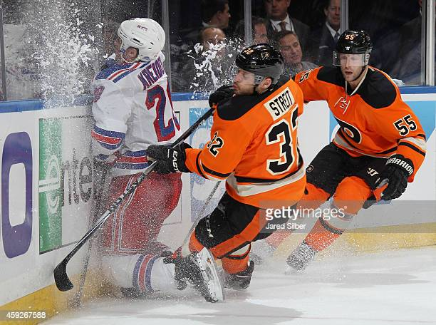 Mark Streit of the Philadelphia Flyers checks Chris Kreider of the New York Rangers into the boards at Madison Square Garden on November 19 2014 in...