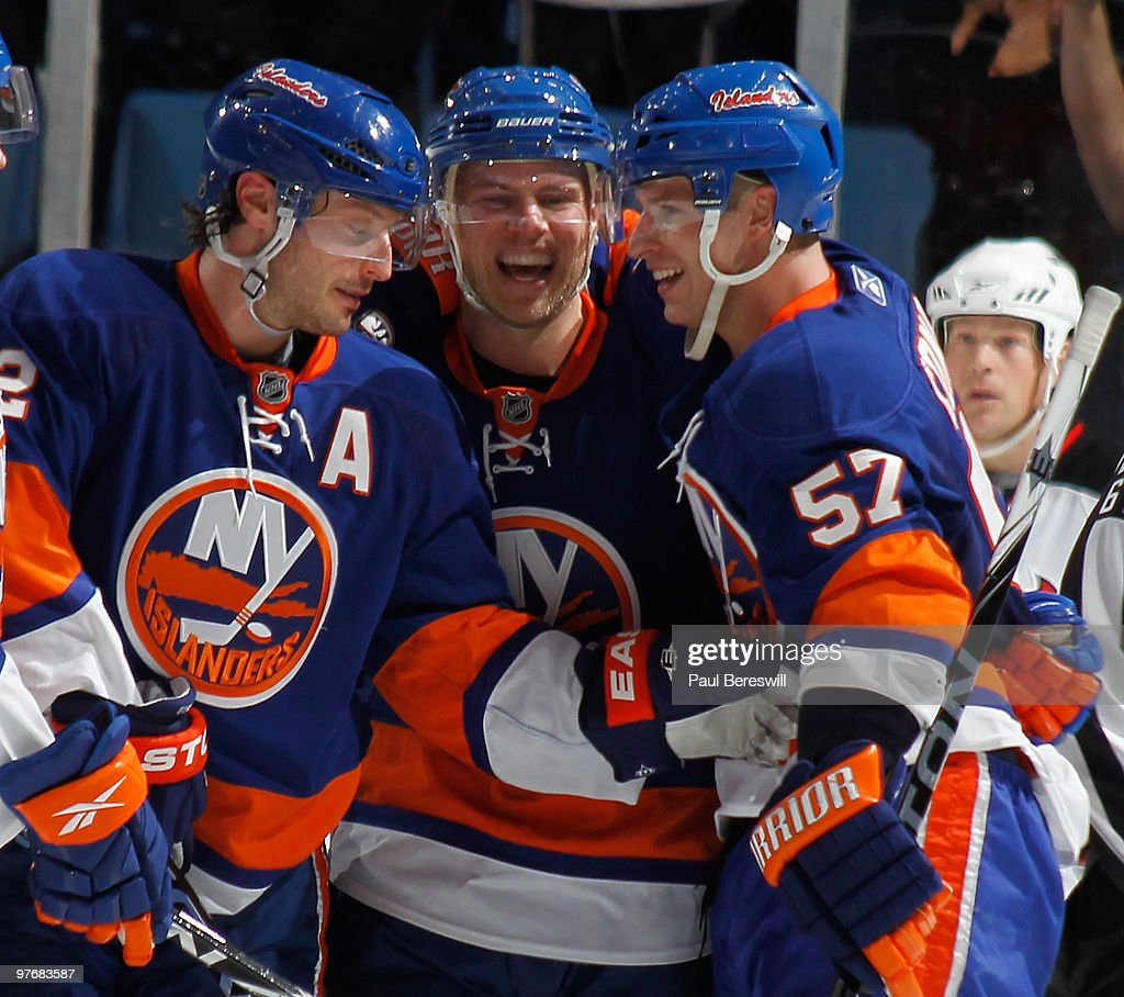 Mark Streit Sean Bergenheim and Blake Comeau of the New York Islanders celebrate a shorthanded goal by Bergenheim in the third period of an NHL game...