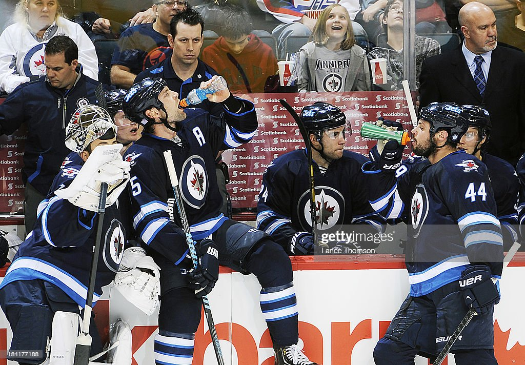 Mark Stuart #5 and Zach Bogosian #44 of the Winnipeg Jets hydrate at the bench during a second period stoppage in play against the Dallas Stars at the MTS Centre on October 11, 2013 in Winnipeg, Manitoba, Canada.