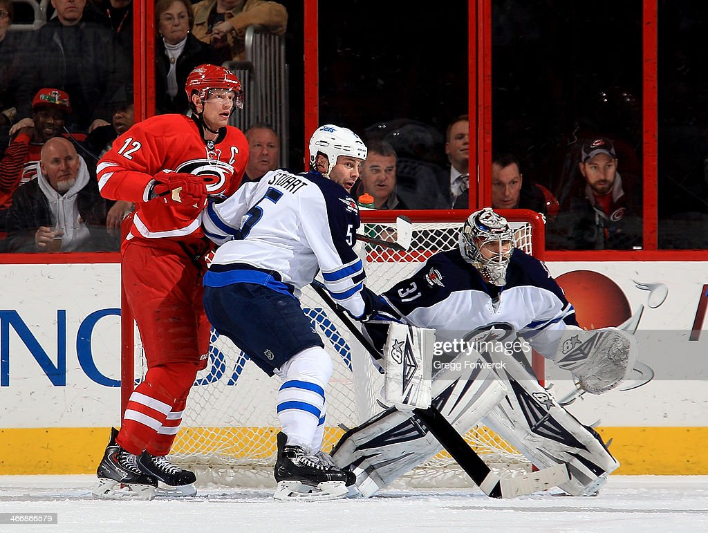 Mark Stuart #5 goaltender Ondrekj Pavelec #31 of the Winnipeg Jets defend the net against <a gi-track='captionPersonalityLinkClicked' href=/galleries/search?phrase=Eric+Staal&family=editorial&specificpeople=202199 ng-click='$event.stopPropagation()'>Eric Staal</a> #12 the Carolina Hurricanes during an NHL game at PNC Arena on February 4, 2014 in Raleigh, North Carolina.