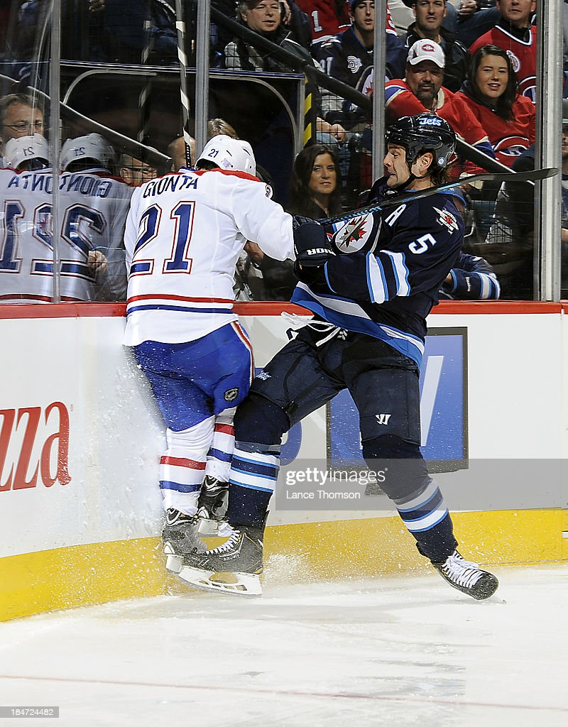 Mark Stuart #5 of the Winnipeg Jets checks <a gi-track='captionPersonalityLinkClicked' href=/galleries/search?phrase=Brian+Gionta&family=editorial&specificpeople=202116 ng-click='$event.stopPropagation()'>Brian Gionta</a> #21 of the Montreal Canadiens into the end boards during third period action at the MTS Centre on October 15, 2013 in Winnipeg, Manitoba, Canada.