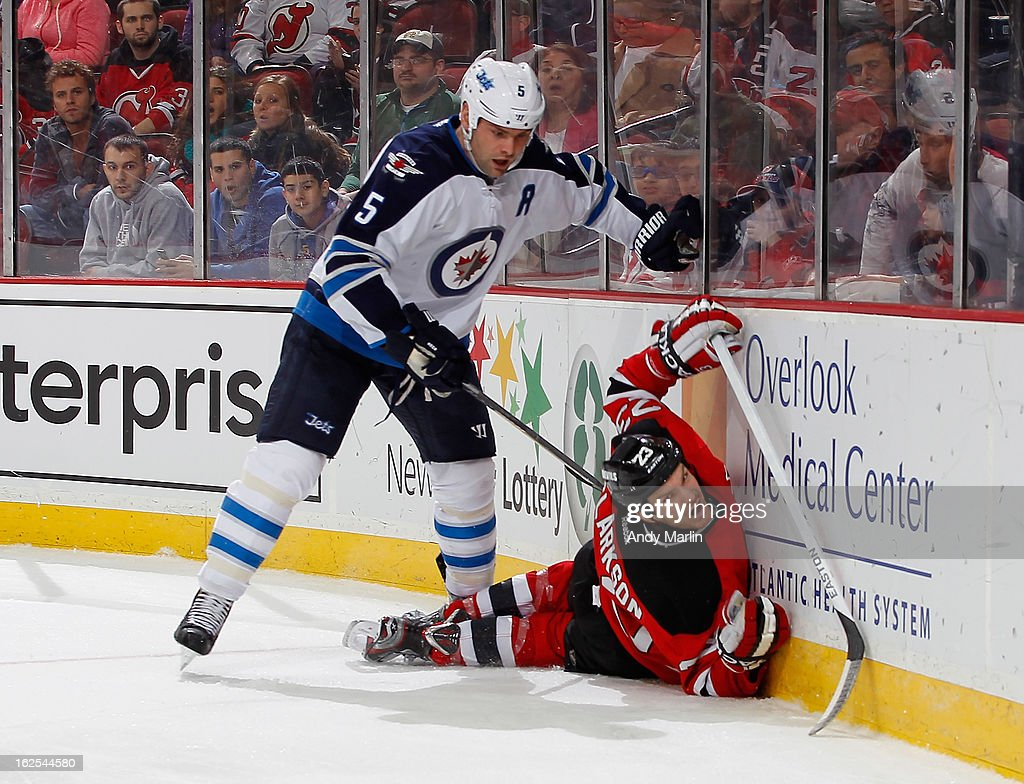 Mark Stuart #5 of the Winnipeg Jets checks David Clarkson #23 of the New Jersey Devils into the boards during the game at the Prudential Center on February 24, 2013 in Newark, New Jersey.