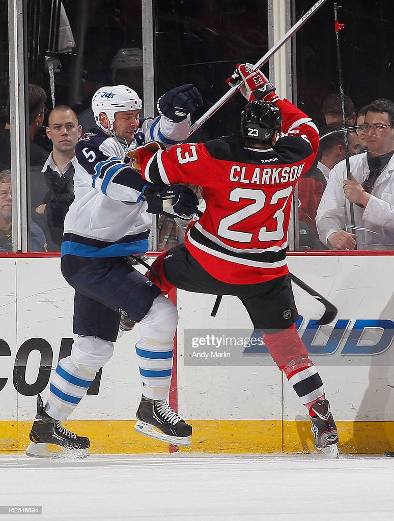 Mark Stuart #5 of the Winnipeg Jets checks David Clarkson #23 of the New Jersey Devils during the game at the Prudential Center on February 24, 2013 in Newark, New Jersey.