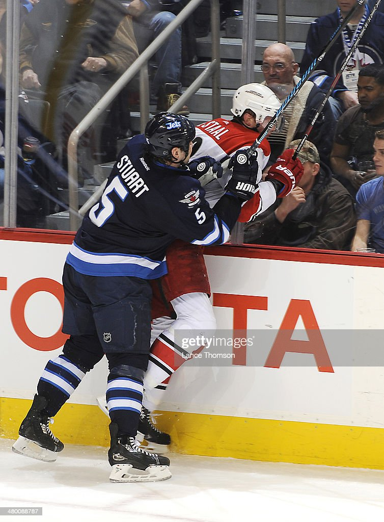 Mark Stuart #5 of the Winnipeg Jets checks <a gi-track='captionPersonalityLinkClicked' href=/galleries/search?phrase=Eric+Staal&family=editorial&specificpeople=202199 ng-click='$event.stopPropagation()'>Eric Staal</a> #12 of the Carolina Hurricanes into the boards during second period action at the MTS Centre on March 22, 2014 in Winnipeg, Manitoba, Canada.