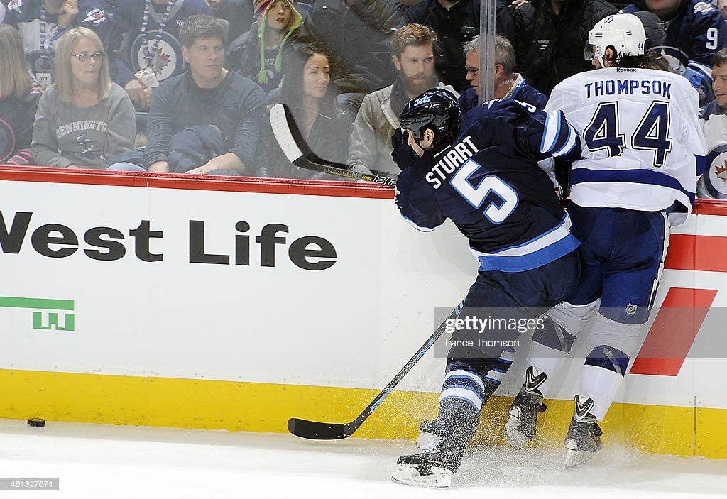 Mark Stuart #5 of the Winnipeg Jets checks Nate Thompson #44 of the Tampa Bay Lightning into the boards as the puck slides down the ice during second period action at the MTS Centre on January 7, 2014 in Winnipeg, Manitoba, Canada.